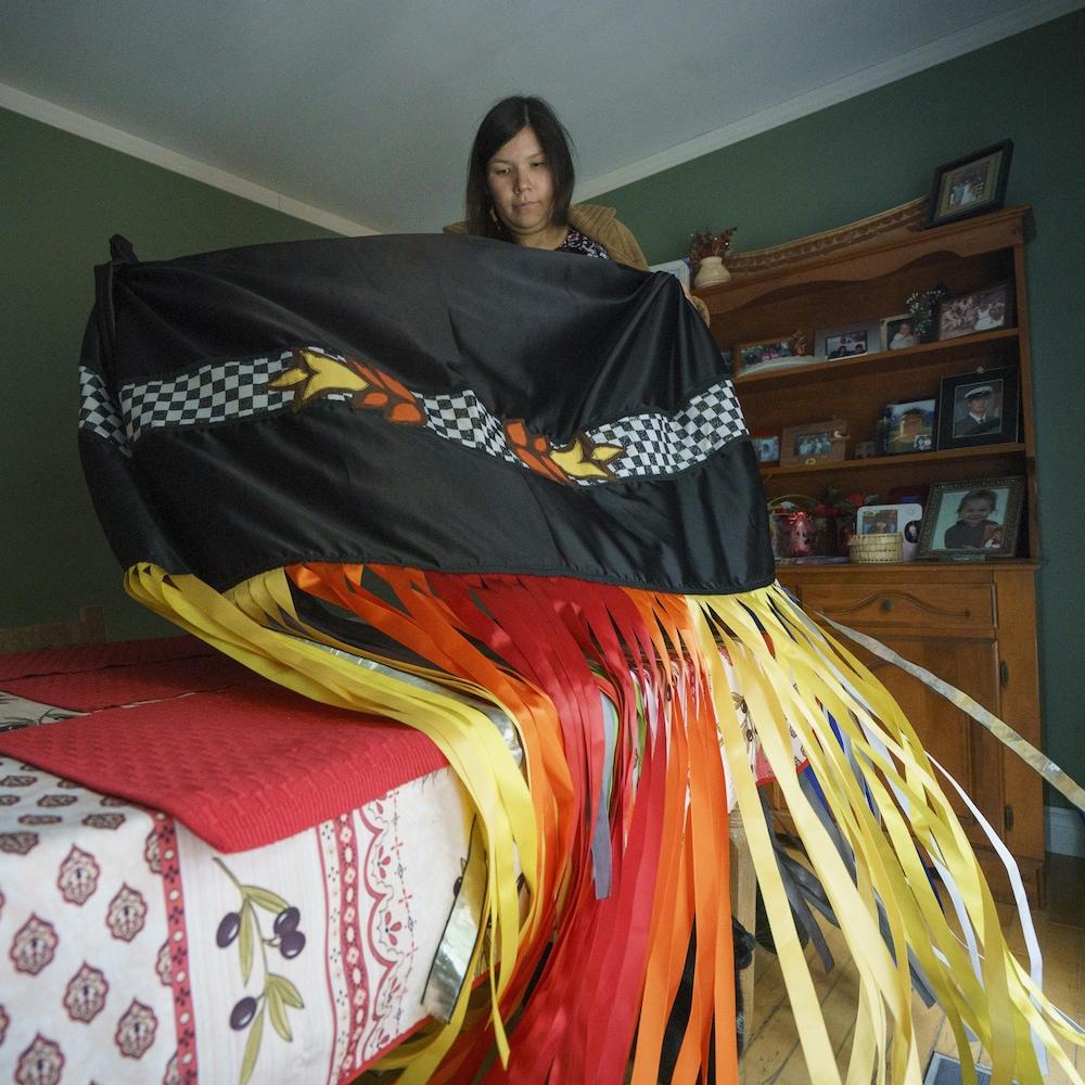 Catherine Boivin, artiste multidisciplinaire et lauréate du prix Manitou-Kiuna 2018 (pour les diplômés en arts), arbore ici un châle (shawl) traditionnel qu'elle porte lorsqu'elle réalise une performance de de « fancy dance », une danse effectuée lors des pow-wow. Le châle se démarque par ses couleurs vives et ses paillettes.