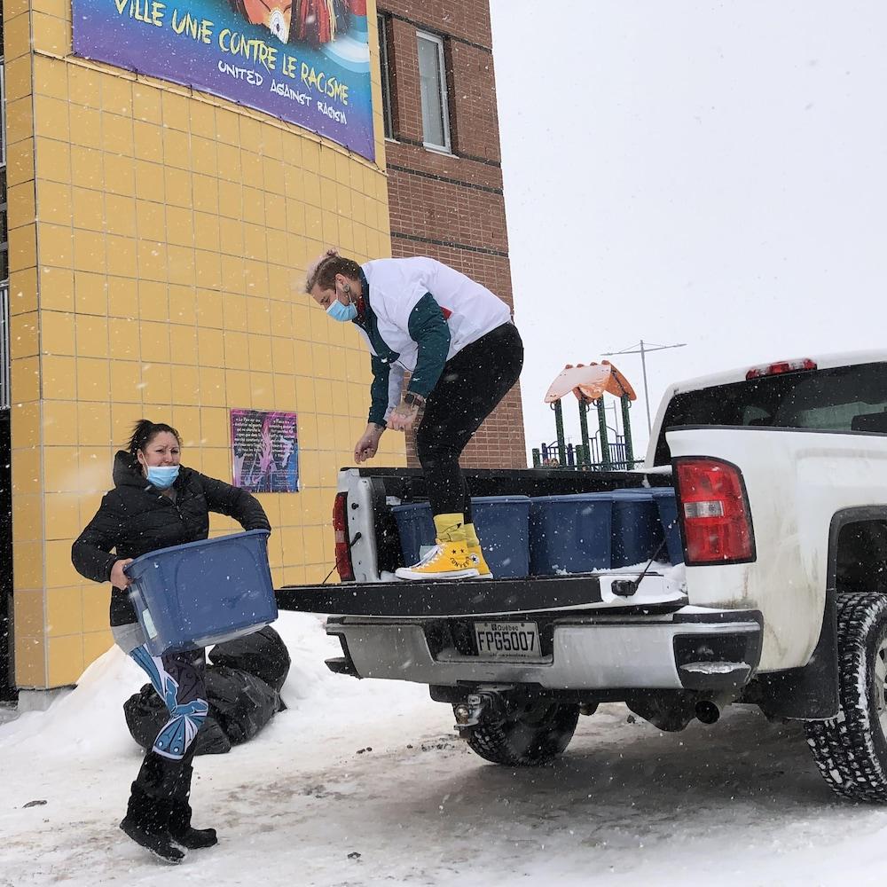 Deux personnes chargent des bacs dans un camion en hiver.