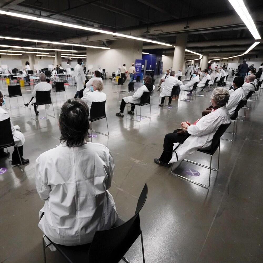 Une grande salle avec de nombreux préposés assis sur des chaises et vêtus tout de blanc.