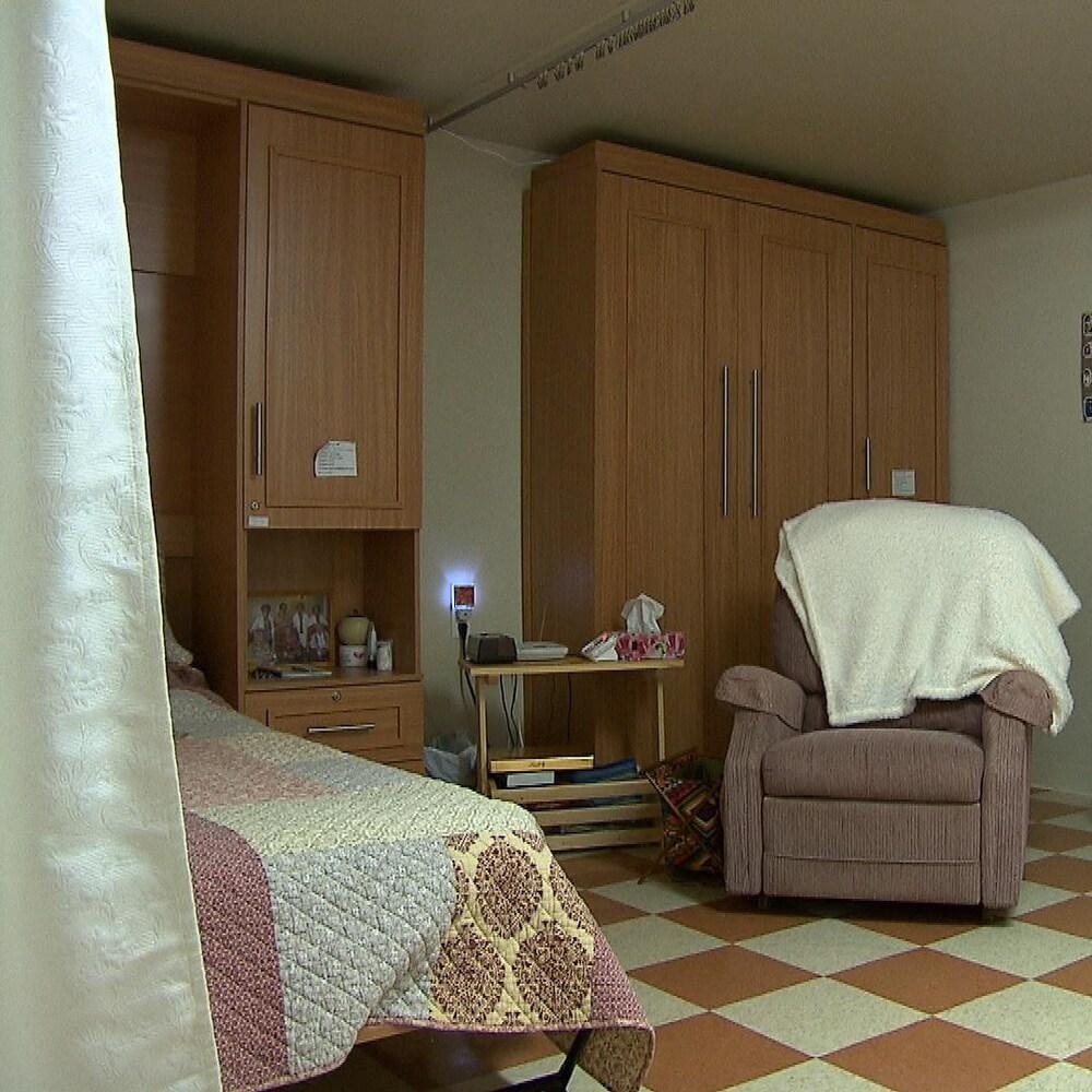 Un système de rideaux posés au plafond sépare certaines chambres des résidents d'une maison pour aînés. Un lit simple, une armoire et un fauteuil se trouvent dans la pièce.