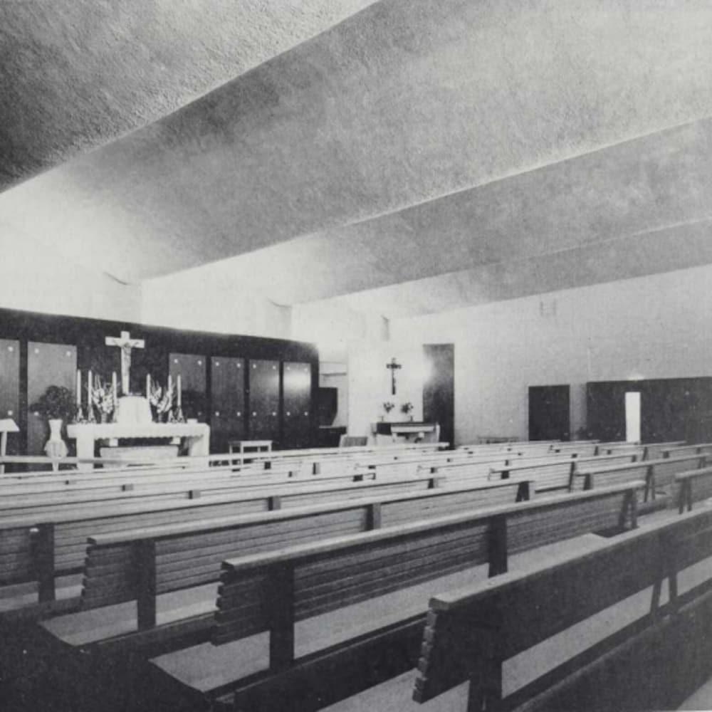 Des bancs d'église alignés devant l'autel.