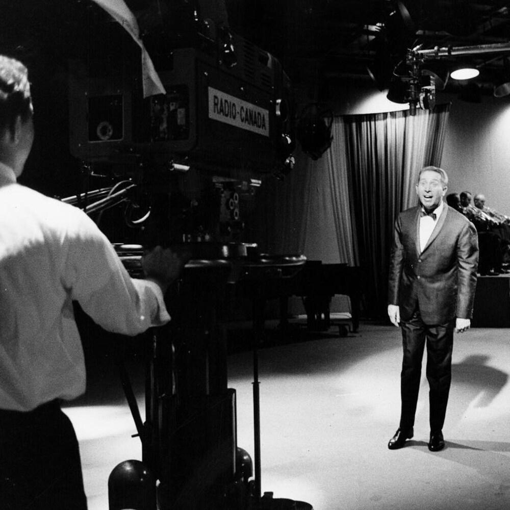 Sur le plateau de l'émission, un caméraman film le chanteur Charles Trenet et derrière, l'orchestre.