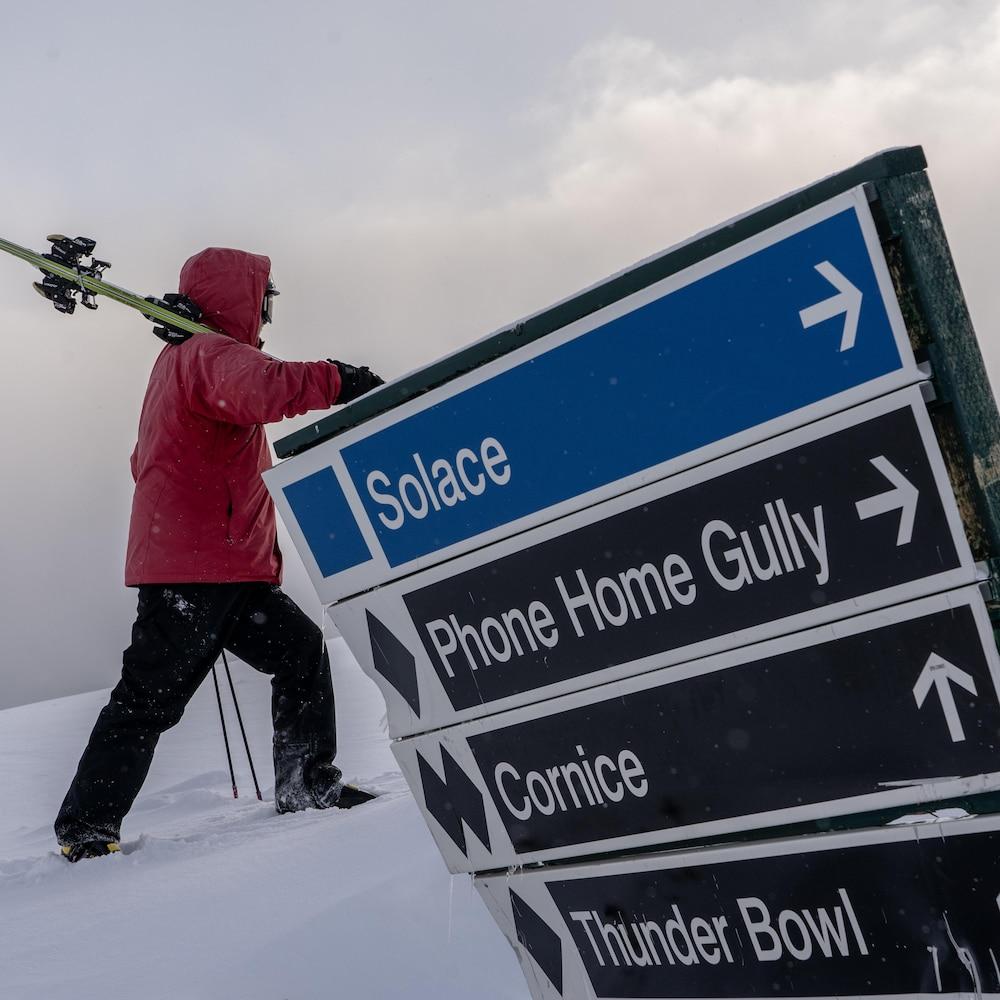 Un homme en habit de ski grimpe une piste avec ses skis dans les bras devant une affiche avec le noms de quatre pistes.