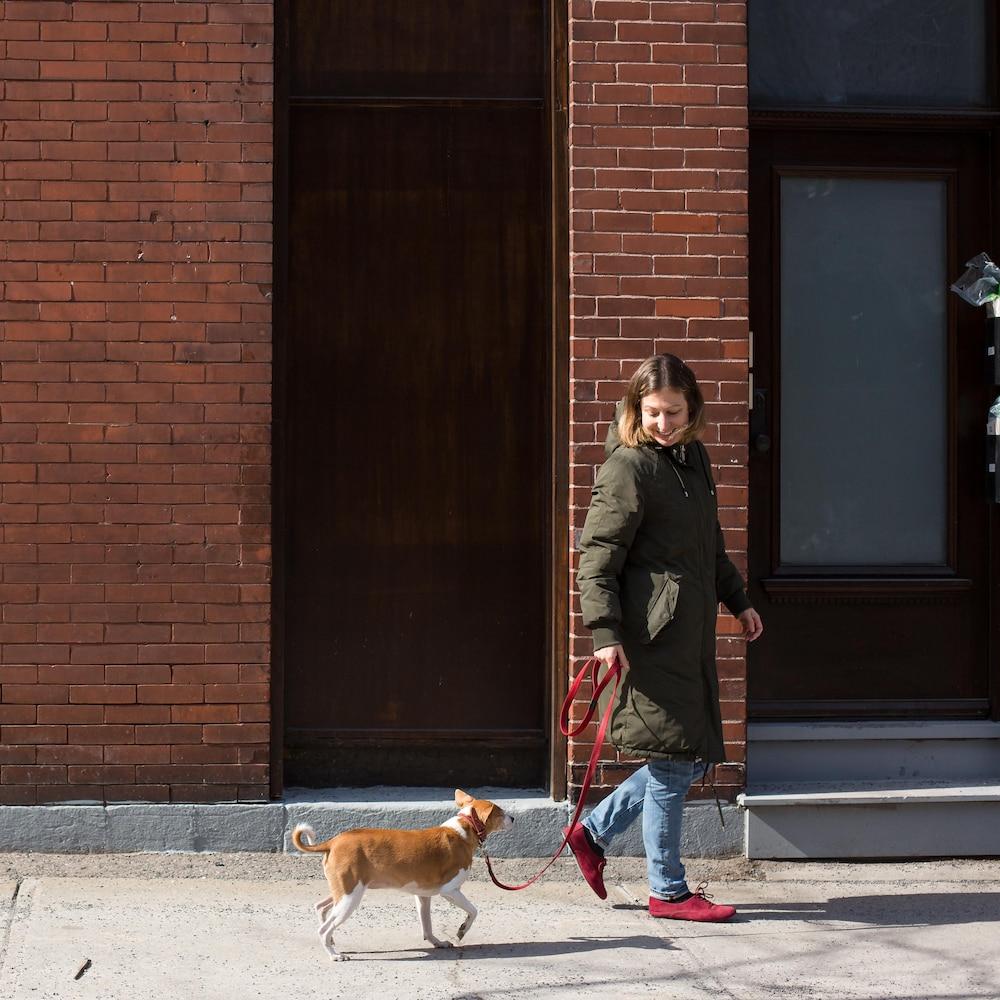 Michèle Nicole Provencher promène son chien Céleri dans une rue de Montréal.