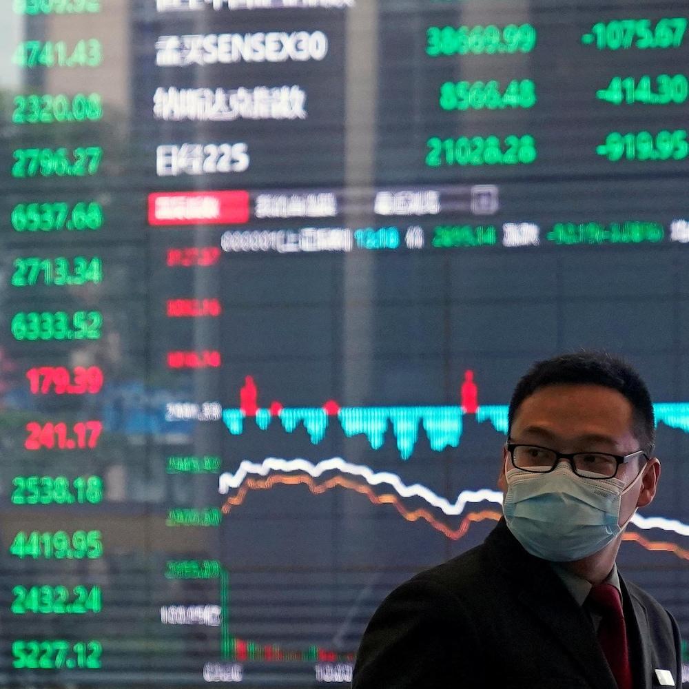 Un homme avec masque protecteur à la Bourse de Shanghai, dans le district financier de Pudong. En toile de fond, un immense tableau numérique présentant l'évolution des cours boursiers.