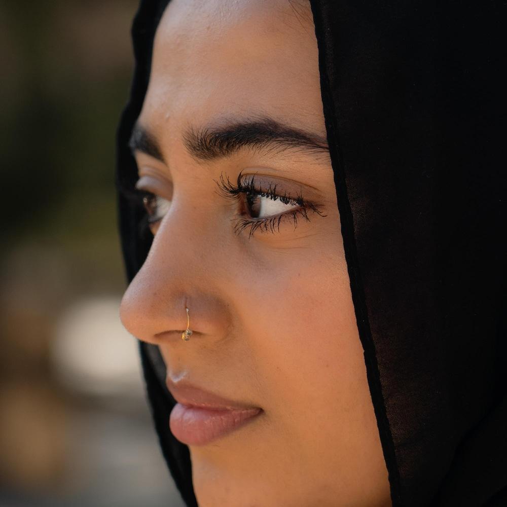 Gros plan sur le visage d'Izza, qui porte un percing sur le nez.