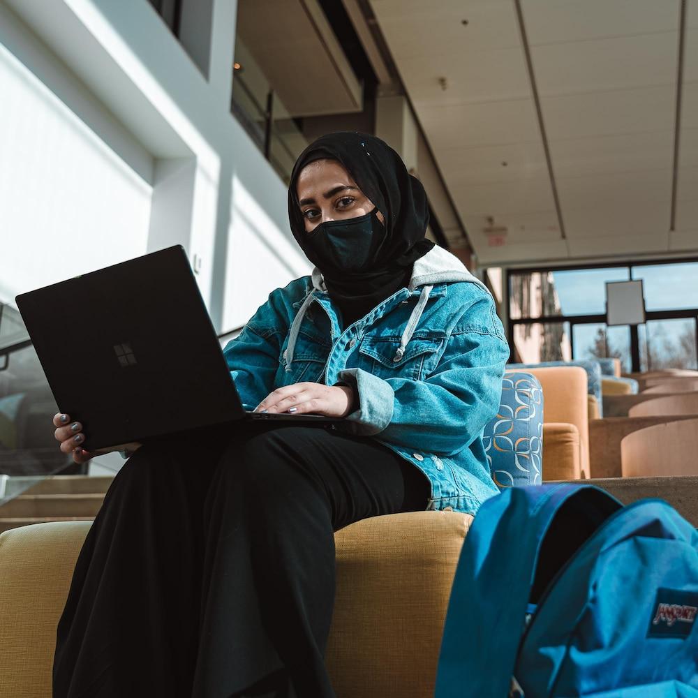 Izza assise dans un amphithéâtre avec un ordinateur portable sur ses jambes. En plus du voile sur ses cheveux, elle porte aussi un masque facial en raisons des mesures sanitaires liées à la pandémie de COVID-19.