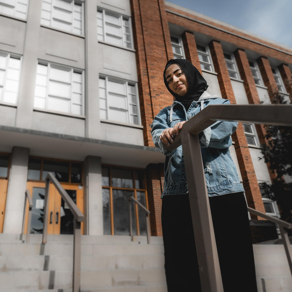 Izza devant la porte de l'université.