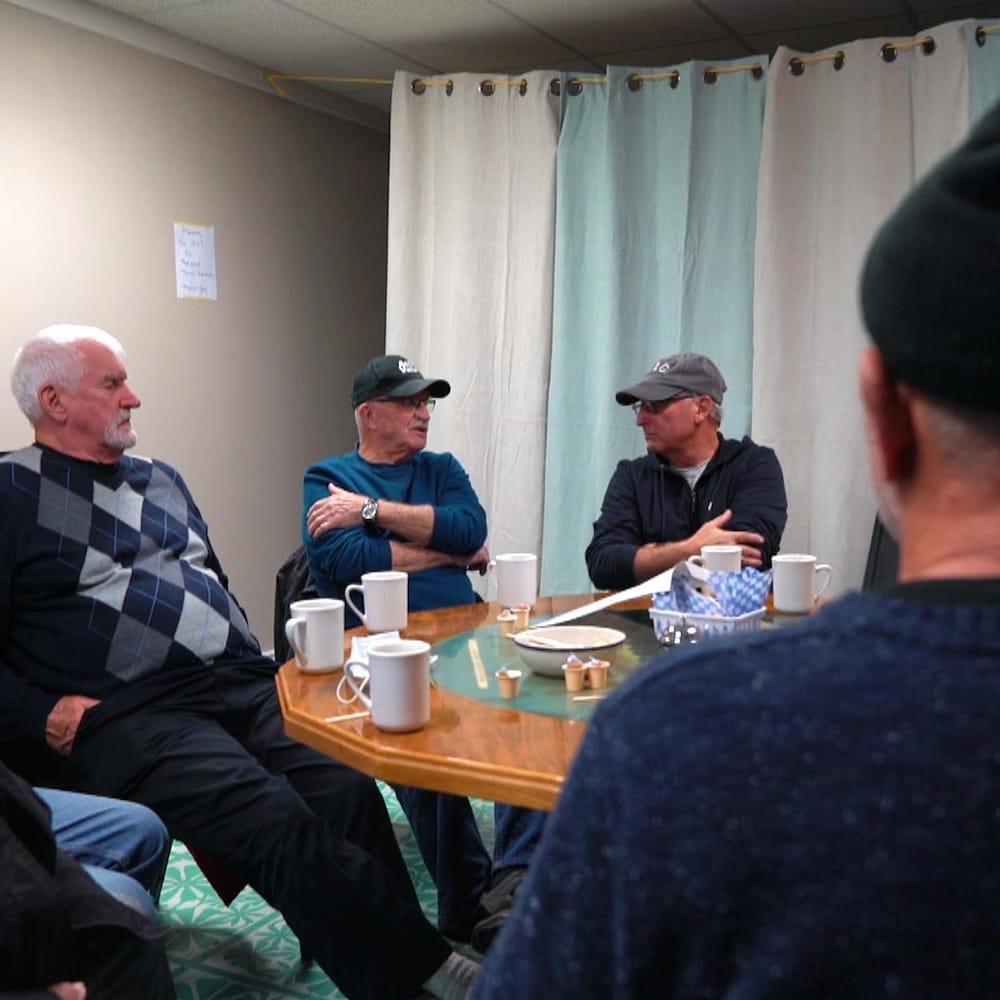 Six hommes autour d'une table sirotant un café.