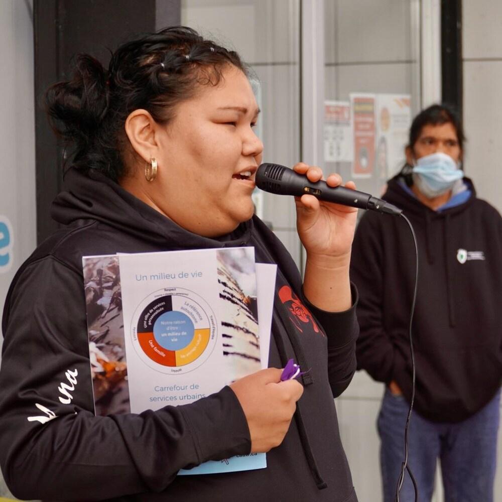 Une femme qui parle au micro devant le Centre d'amitié autochtone de Trois-Rivières.