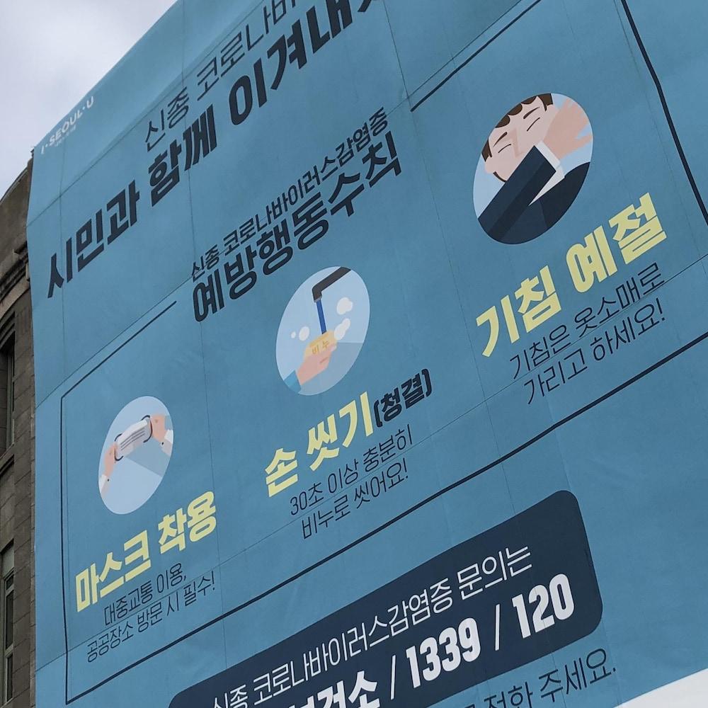 Une affiche géante rappelle les consignes des autorités sanitaires.