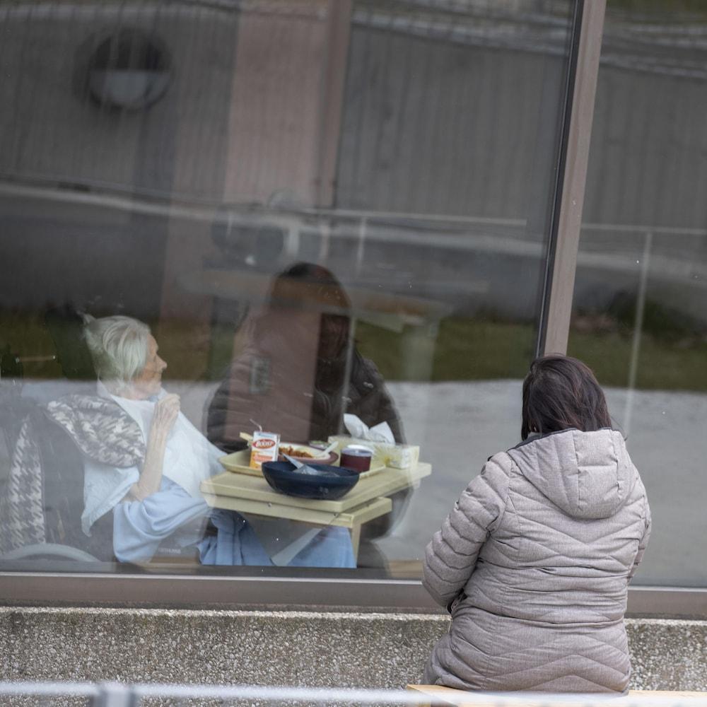 Une femme observe par la fenêtre d'un CHSLD une patiente qui attend qu'une préposée, revêtant un équipement de protection et un masque, lui serve un repas.