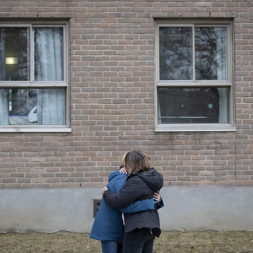 Un couple enlacé devant un mur fenestré.