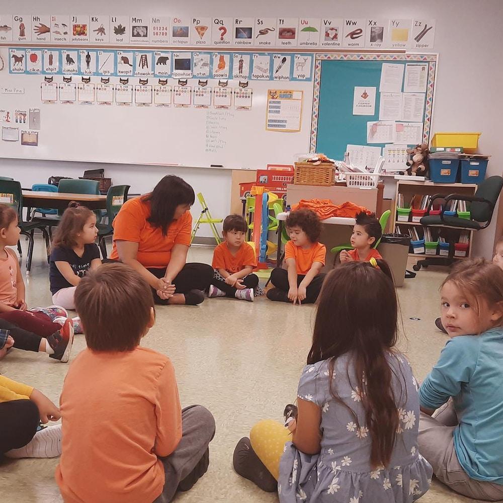 Des enfants en cercle dans une salle de classe avec leur enseignante.