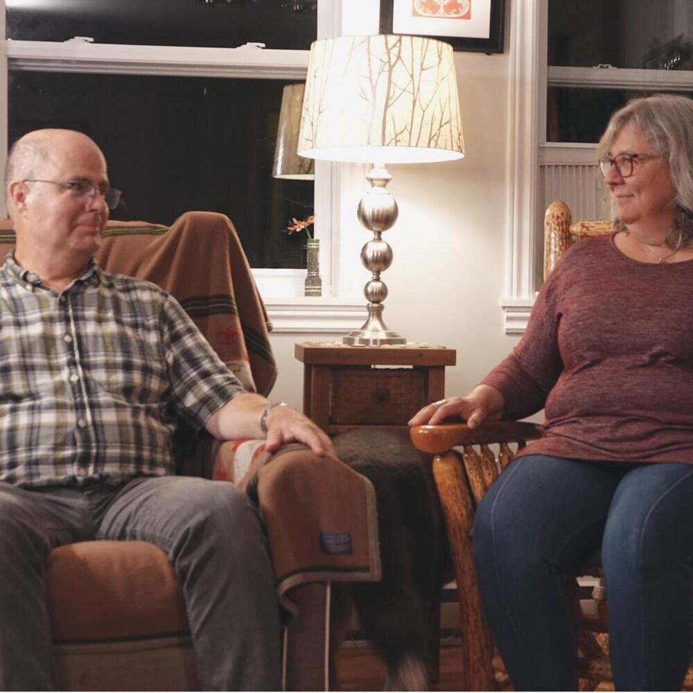 Lisa Perley-Dutcher et Stephen Dutcher dans leur salon avec leur chien.