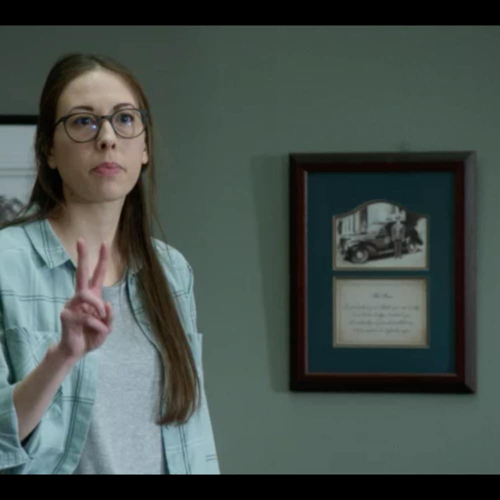 L'actrice fait le chiffre 2 avec ses doigts.