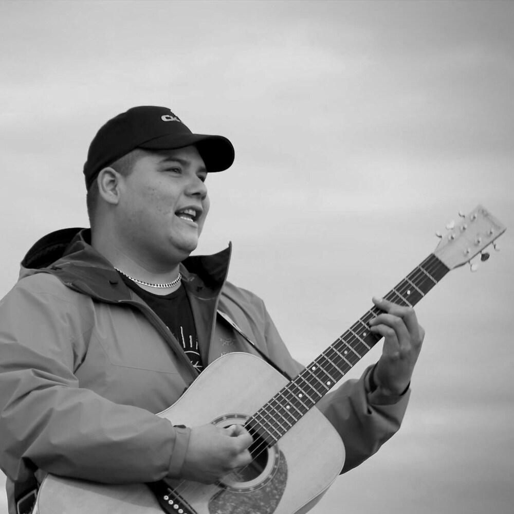 Dan-Georges avec sa guitare à l'extérieur.