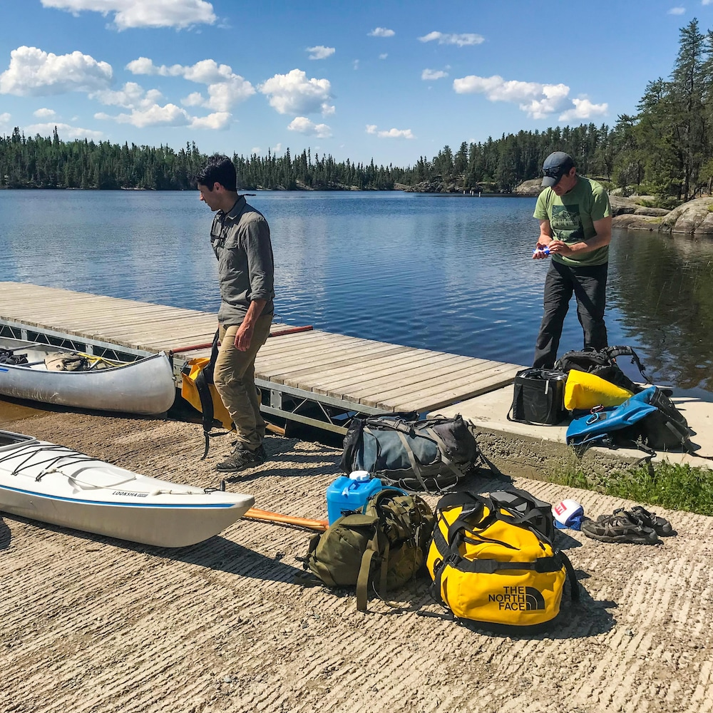 Deux hommes se préparent à embarquer dans un canot