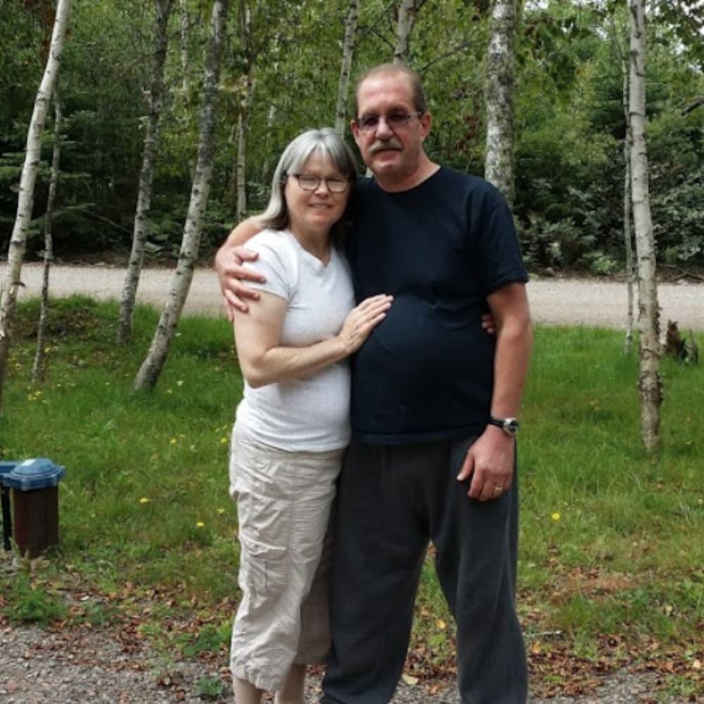 Frank entoure Dawn de son bras pour prendre une pose devant la caméra. Ils se trouvent devant une forêt pour la photo.