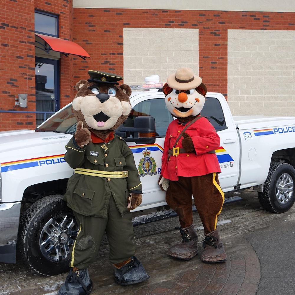 Les mascottes du 41e Déjeuner des agents de la paix au profit de la Société canadienne du cancer posent fièrement devant un véhicule de la GRC.
