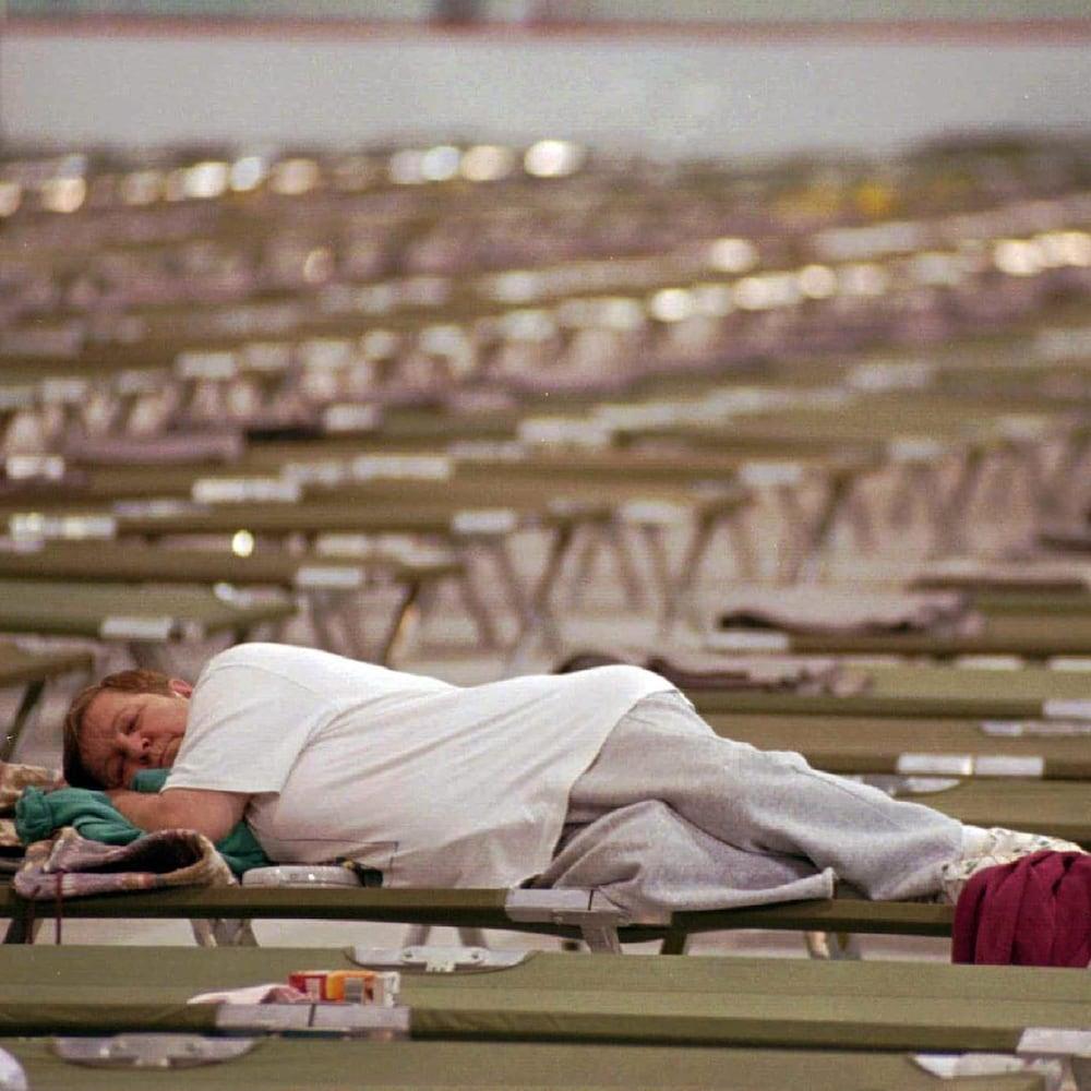 Une femme dort sur un lit de camp.