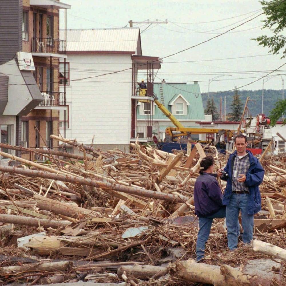Deux personnes se tiennent à travers des débris d'arbres dans une rue du secteur Grande-Baie, à Saguenay.