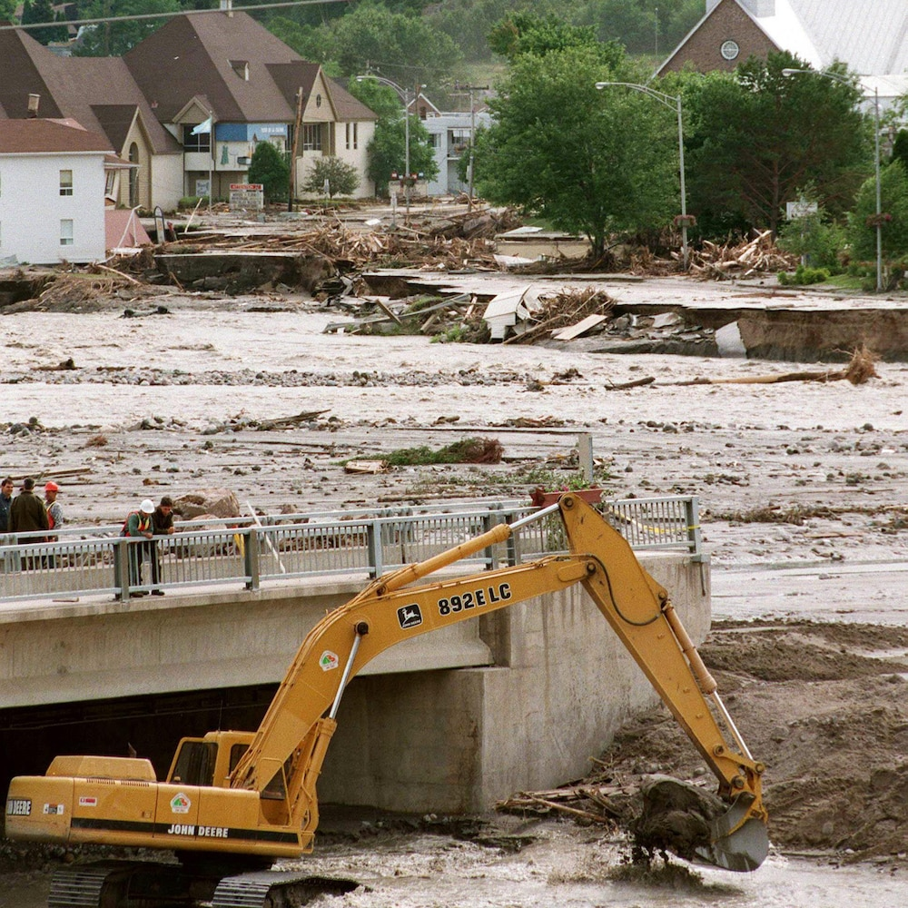 Une pelle mécanique est dans la rivière pour reconstruire la route reliant le secteur de Grande-Baie au reste de la ville.