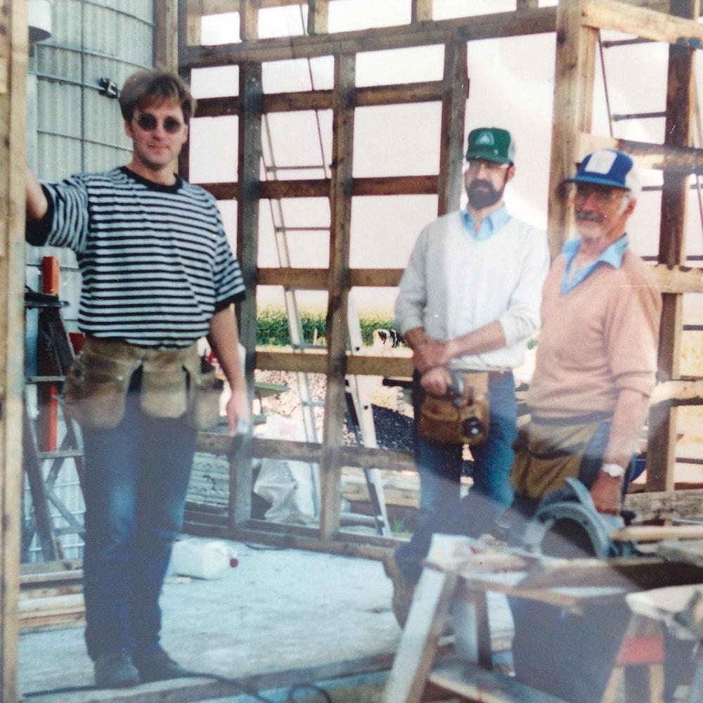 Denis, Alain et Florian prennent la pose dans un échafaudage de bois.
