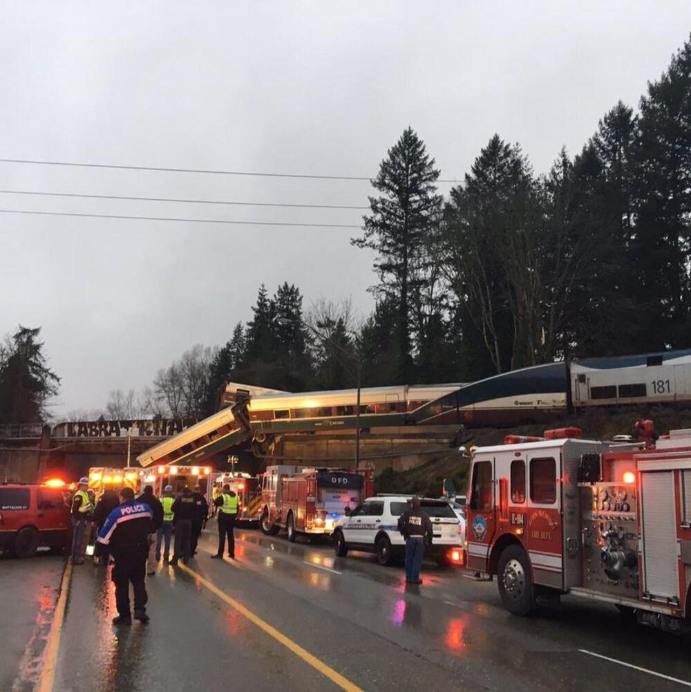 La scène de l'accident vu de la route avec les secouristes et camions de pompier en premier plan.