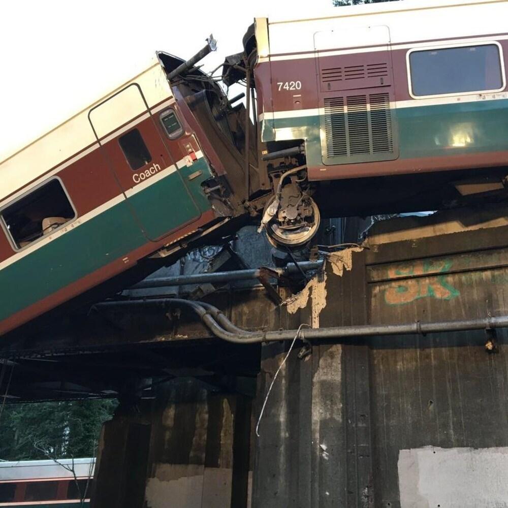 Un des wagons qui a quitté les rails pend par dessus le garde fou d'un viaduc.