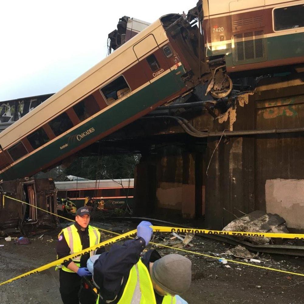 Deux premiers répondants devant des wagons de train qui ont déraillé.