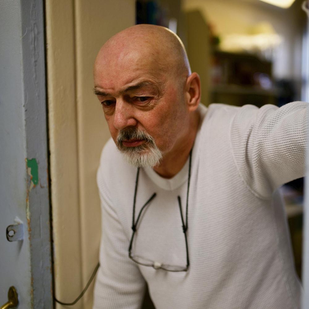 Daniel Jolivet se tient à l'aide d'une canne et le cadre de la porte de sa cellule.