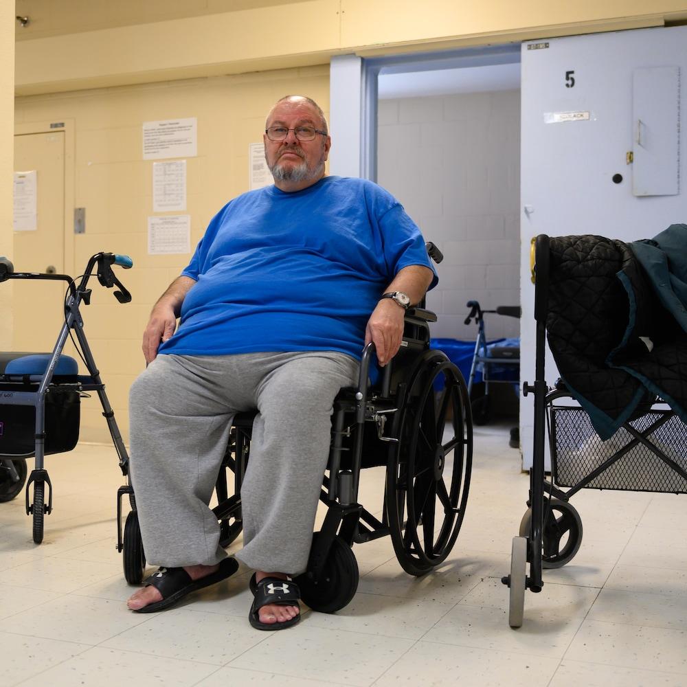 Le détenu Daniel Rozon dans son fauteuil roulant à l'extérieur d'une cellule.