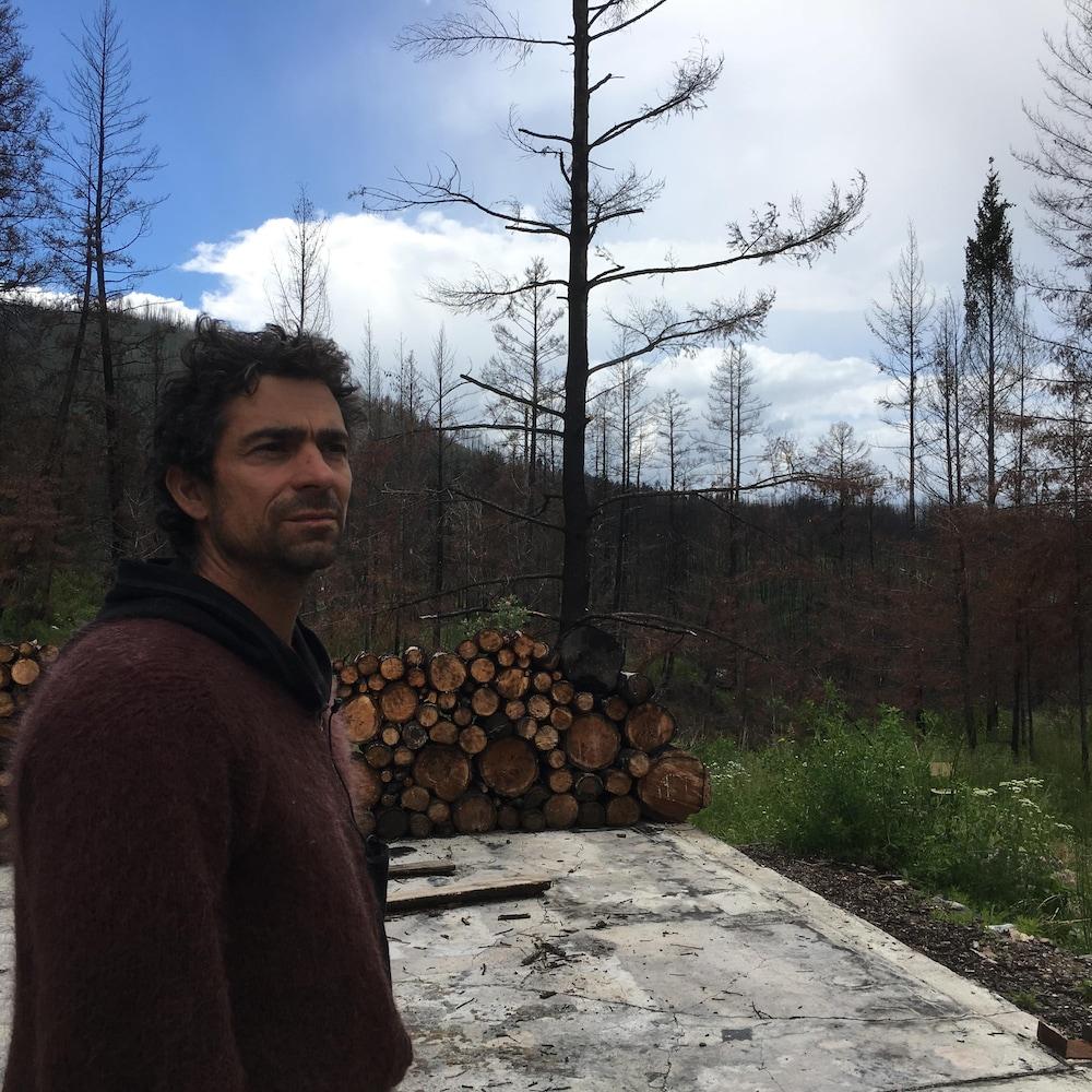 Un homme devant une dalle de ciment qui rappelle qu'une maison s'y trouvait auparavant. Une corde de bois à côté et des troncs d'arbres brûlés mais encore debout.