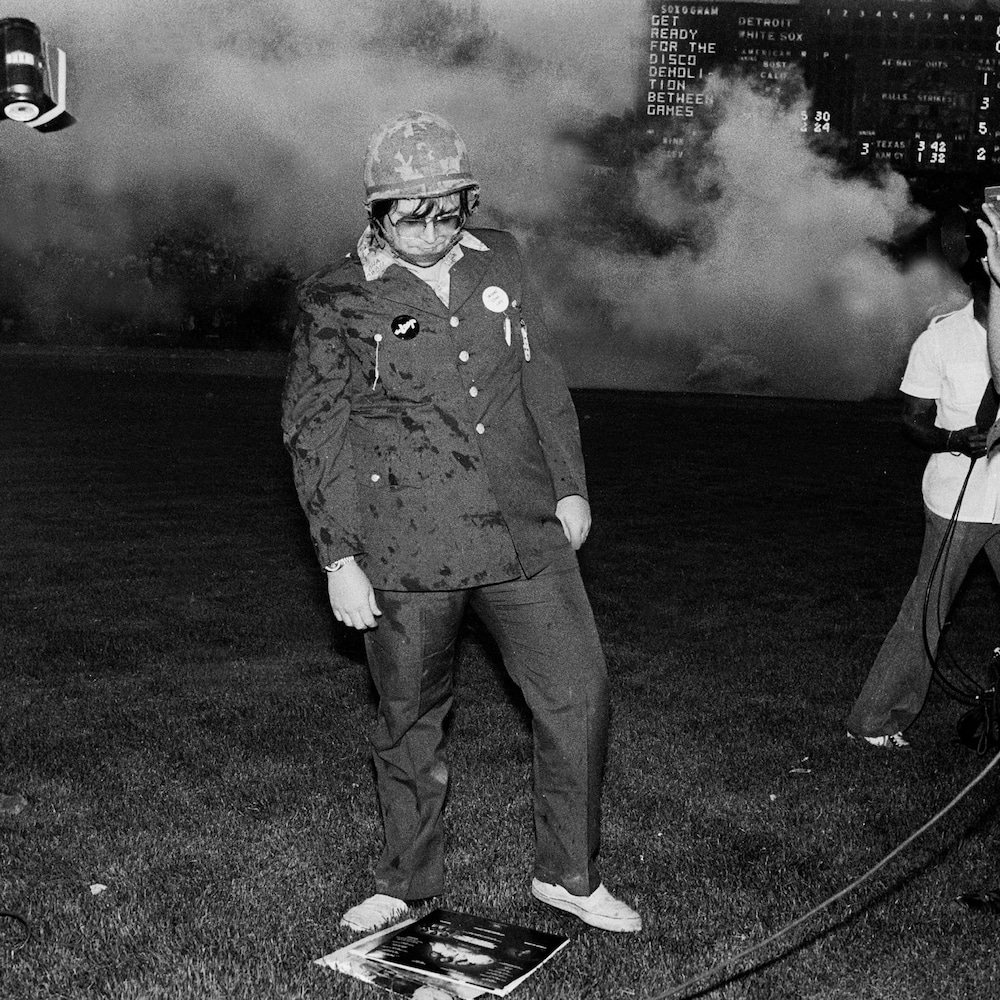 Steve Dahl jette un regard de dédain à des vinyles disco étalés sur la pelouse  du stade de baseball des White Sox de Chicago.