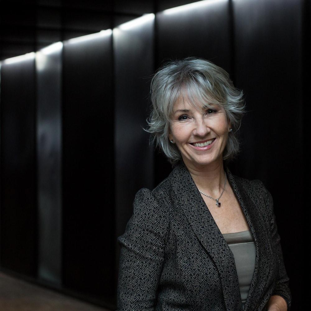 Portrait de Judi Richards, posant dans un corridor.