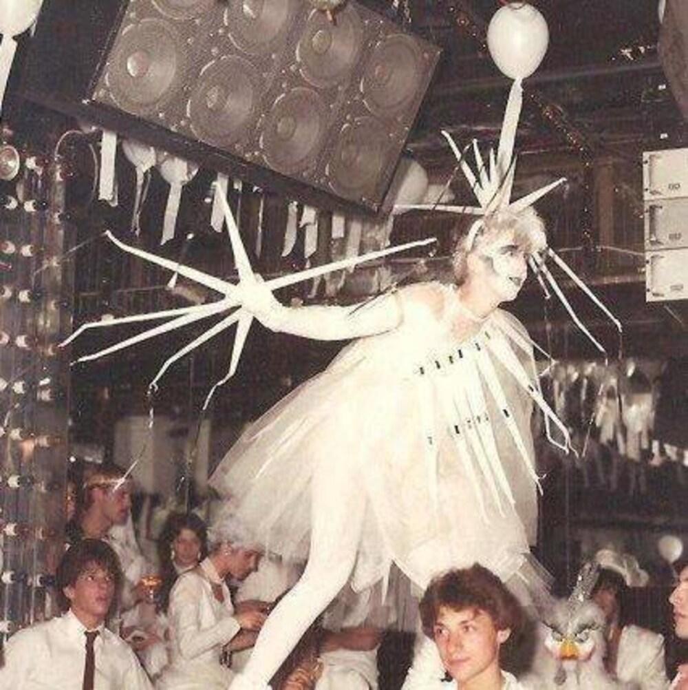 Une personne costumée en blanc danse sur une table dans une discothèque.