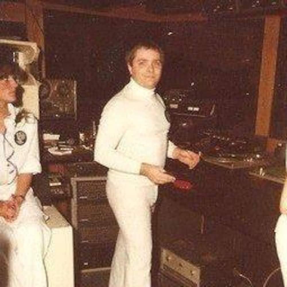 Tout vêtu de blanc, Robert Ouimet prend la pose dans la cabine où il mixe la musique.
