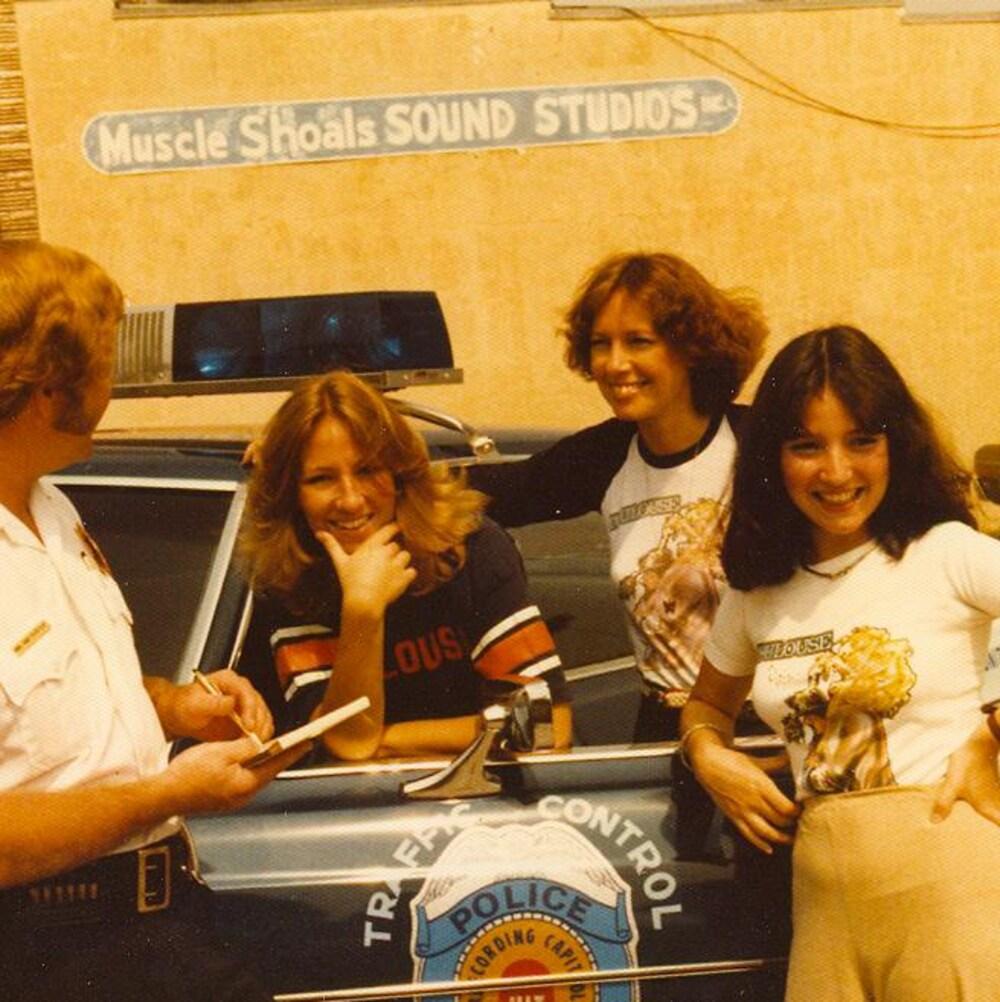 Les chanteuses de Toulouse sourient pour la caméra, à côté d'une voiture de police.