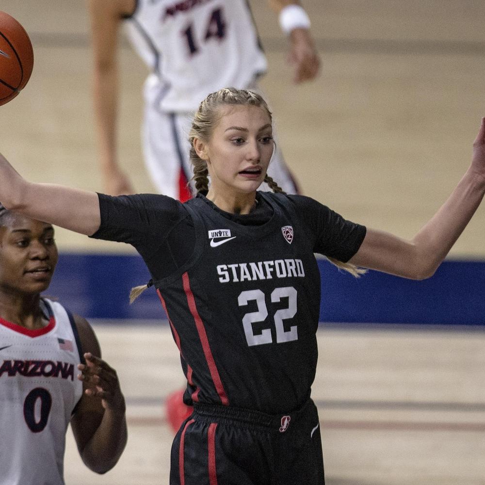 Une joueuse de basketball tient un ballon d'une main en regardant une coéquipière.