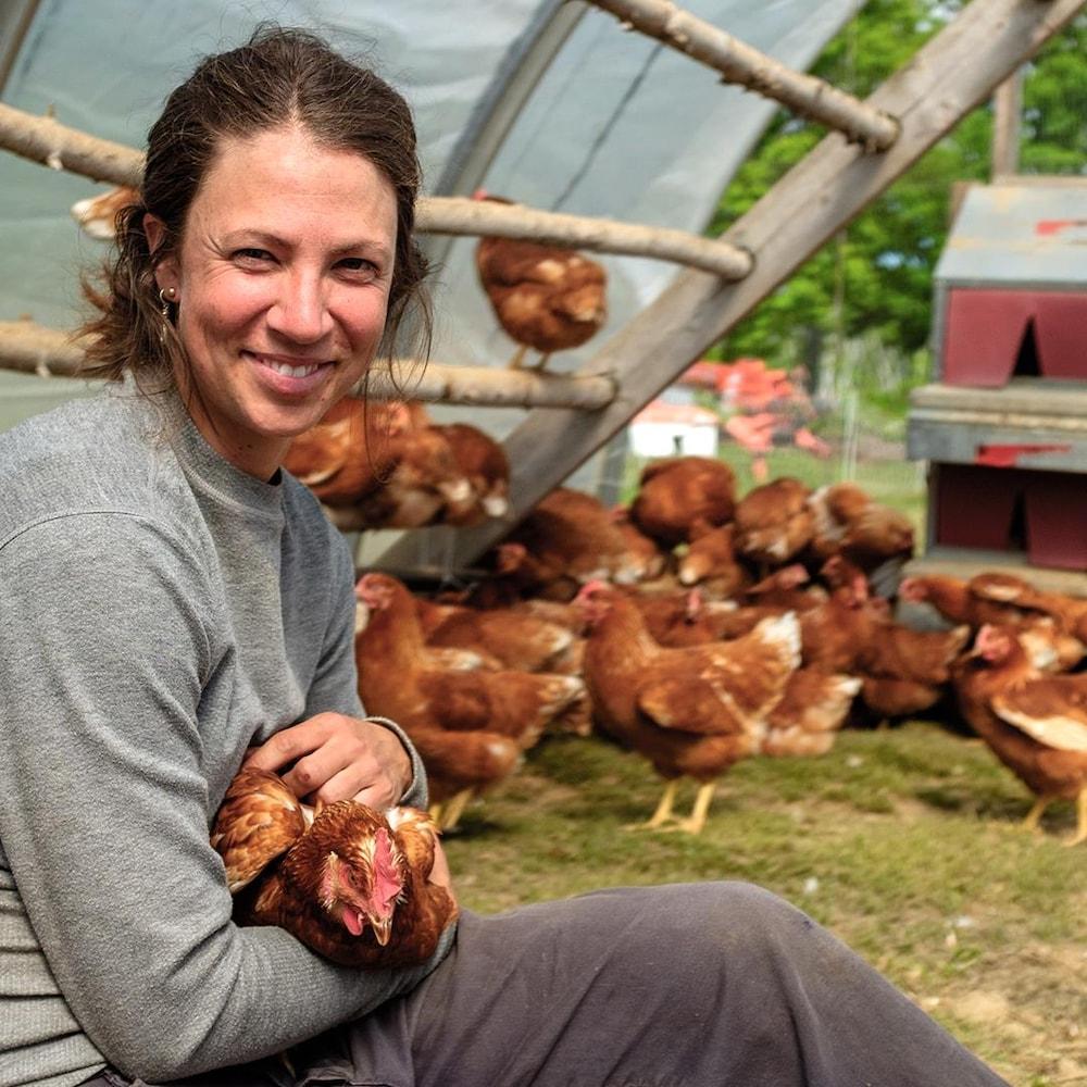 Rébeka Fraser-Chiasson entourée de poules en tient une dans ses bras.