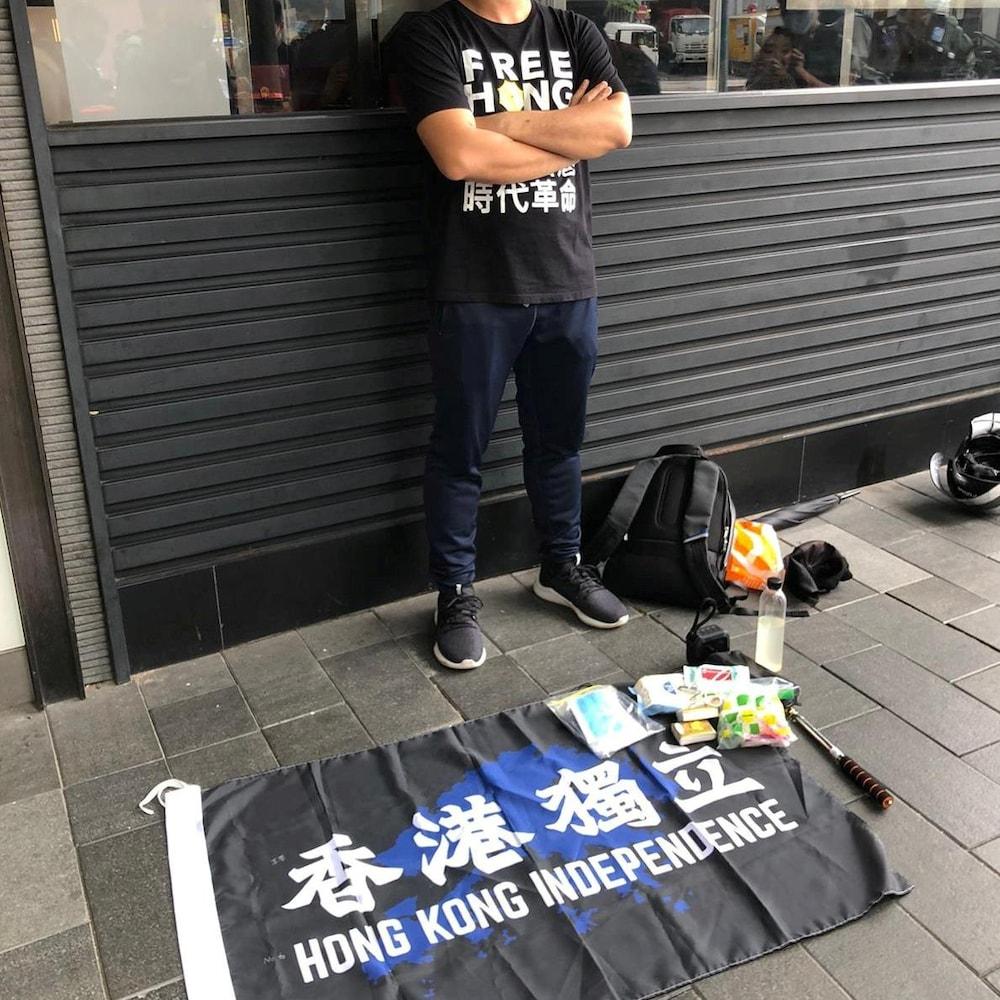 Un homme debout à côté d'un drapeau sur lequel on peut lire « Indépendance de Hong Kong ».
