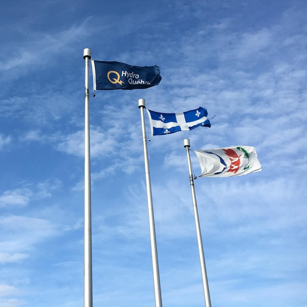 Des drapeaux d'Hydro-Québec, du Québec et du Gouvernement régional Eeyou-Istchee Baie-James.