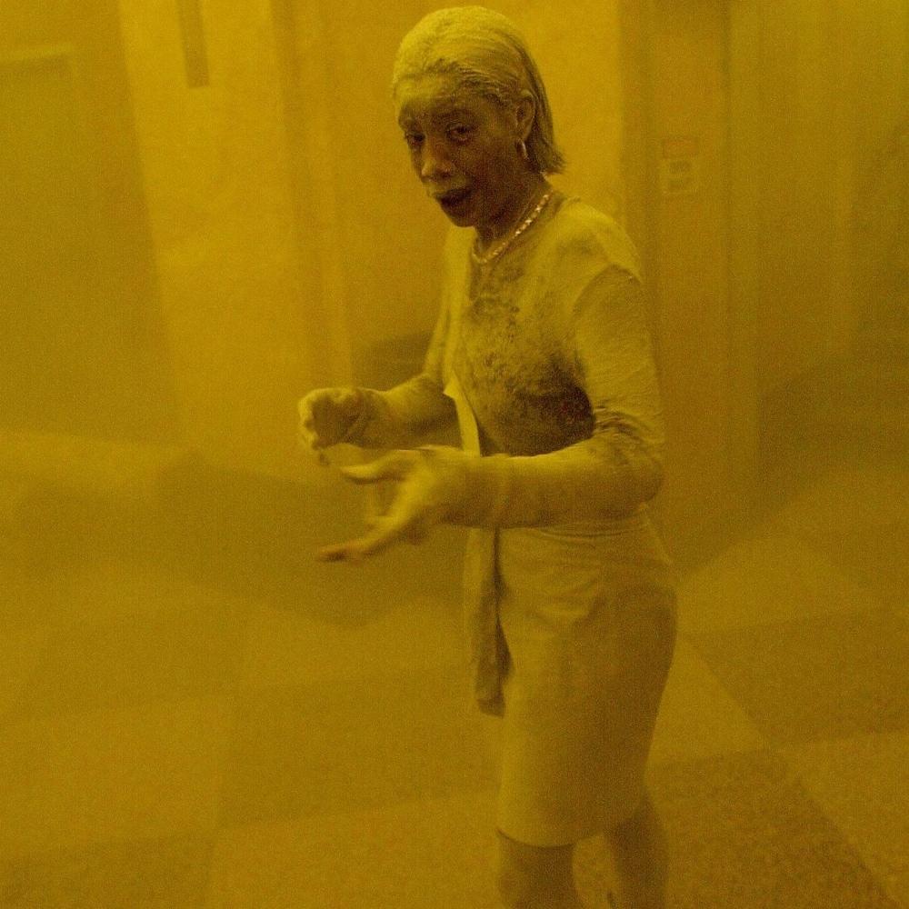 On voit une femme debout en tailleur couverte de suie blanche dans un hall où flotte encore de la poussière, rendant la vision un peu opaque. Elle a le regard ébahi et fixe l'objectif.