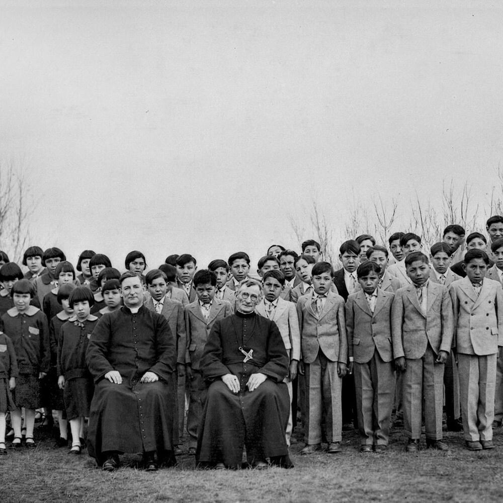 Des élèves de l'École Brocket, en Alberta, en 1930, sont debout en uniformes d'élèves derrière deux religieux assis.