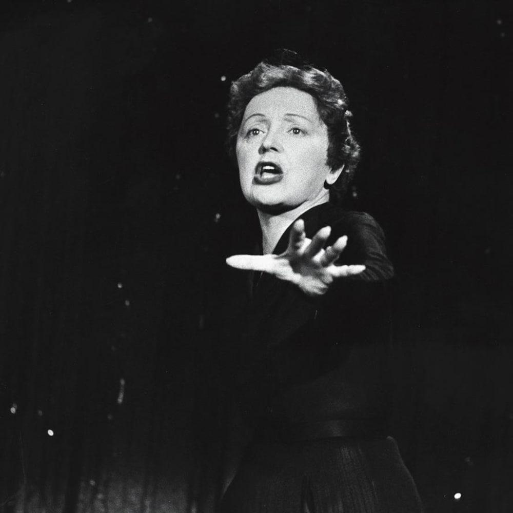La chanteuse Édith Piaf, en performance, une main tendue devant elle.