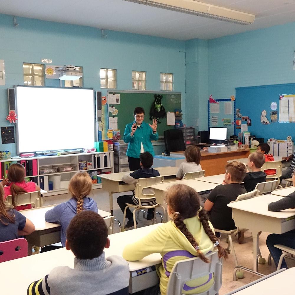 Des enfants assis en classe regarde une interlocutrice qui fait une présentation à l'avant.