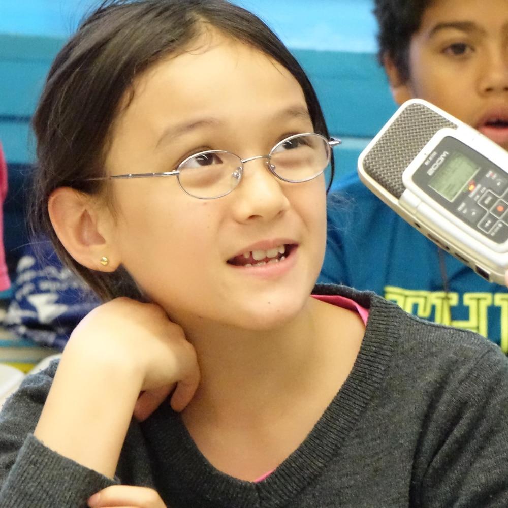 Un enfant d'une dizaine d'année parle dans un micro d'enregistrement portatif.