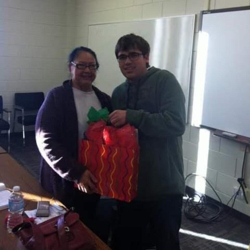 Cameron Adams offre un cadeau à Florence Paynter dans une salle de classe.