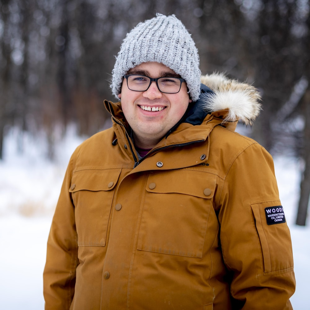 Cameron Adams sourit en extérieur, dans une zone enneigée.